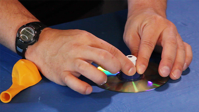 Press the sports bottle cap to the CD and hold it for a few moments while the glue sets up.